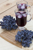 Grape juice cooler with ice in glass and glass of fresh blue grapes on a wooden table Royalty Free Stock Photo