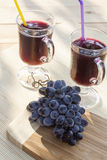 Grape juice cooler with ice in glass and glass of fresh blue grapes on a wooden table Stock Photo