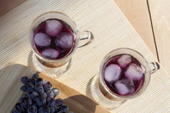 Grape juice cooler with ice in glass and glass of fresh blue grapes on a wooden table Stock Photos