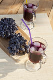 Grape juice cooler with ice in glass and glass of fresh blue grapes on a wooden table Royalty Free Stock Images