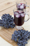 Grape juice cooler with ice in glass and glass of fresh blue grapes on a wooden table Royalty Free Stock Photos