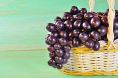 Grape and leaves in basket on wooden table Stock Images