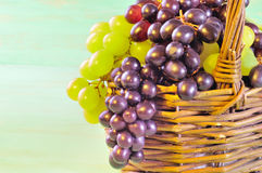 Grape and leaves in basket on wooden table Stock Image