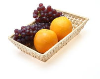 Grape and orange in a basket Stock Image