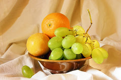 Grape, orange and plum in a vase Royalty Free Stock Image