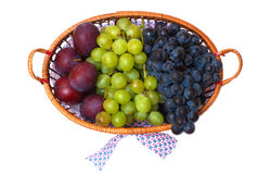 Grape and plums in the basket isolated Royalty Free Stock Image