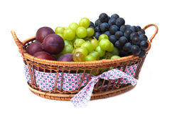 Grape and plums in the basket isolated Royalty Free Stock Photography