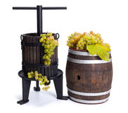 Grape pressing utensil and barrel with white grapes stock image