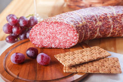Grape and sausages on wooden table. Close up stock image