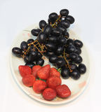Grape and strawberry on a plate. Stock Images