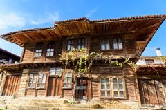 Grape vine over an old traditional rustic house in Zheravna, Bulgaria. Low angle view of the front side of old traditional rustic house made of wood and covered stock photography