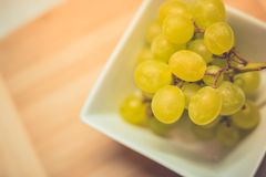 Grape in white bowl on wooden table. Vintage toned grapes in white bowl on wooden table Royalty Free Stock Photos
