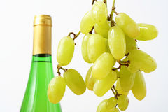 Grape and Wine. A bunch of grapes with a bottle of wine in the background stock photography