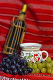 Grape and wine. Bottle of red and white and red grape and a mug of wine on a traditional Romanian carpet Royalty Free Stock Photos