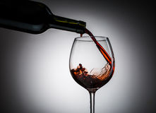Grape wine poured from bottle into wine glass from glass. On blank background Royalty Free Stock Photography