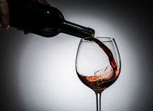 Grape wine poured from bottle into wine glass from glass Stock Image