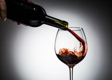 Grape wine poured from bottle into wine glass from glass Royalty Free Stock Photos