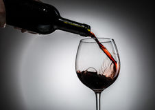 Grape wine poured from bottle into wine glass from glass Stock Images
