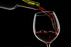 Grape wine poured into wine glass on black background Stock Image