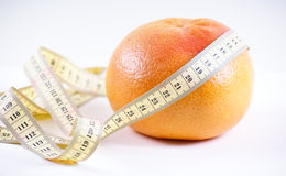 Grapefruit. In the measuring tape, is isolated on a white Royalty Free Stock Images