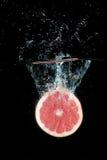 Grapefruit. Water splash half of grapefruit  on black background Royalty Free Stock Photo