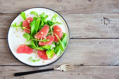 Grapefruit and arugula salad. With pine nuts on wooden table, copy space. Raw vegan vegetarian spring citrus detox salad, healthy food stock photo