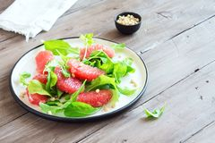 Grapefruit and arugula salad. With pine nuts on wooden table, copy space. Raw vegan vegetarian spring citrus detox salad, healthy food stock images