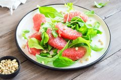 Grapefruit and arugula salad. With pine nuts on wooden table, copy space. Raw vegan vegetarian spring citrus detox salad, healthy food royalty free stock photography