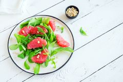 Grapefruit and arugula salad. With pine nuts on wooden table, copy space. Raw vegan vegetarian spring citrus detox salad, healthy food stock photography