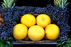 Grapefruit and black grapes. Beautiful fruit arrangement at the grocery Stock Photography