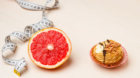 Grapefruit and cake with measuring tape. Diet Royalty Free Stock Photography
