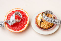 Grapefruit and cake with measuring tape. Diet Stock Photo