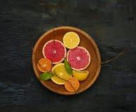 Grapefruit citrus fruit halves on wooden plate Stock Images