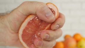Grapefruit Close Up Image with Hand Pressing Half of Fruit and Squeeze the Juice royalty free stock images