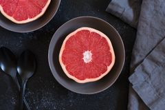 Grapefruit halves in bowls on a table. A grapefruit cut in half and served in grey bowls on gray background royalty free stock image