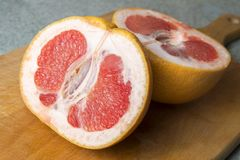 Grapefruit cut into two parts. Red grapefruit cut into two parts in the kitchen desk royalty free stock photos