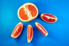 Grapefruit die in de helft op een blauwe achtergrond wordt gesneden royalty-vrije stock fotografie
