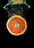 Grapefruit die in water valt stock afbeelding