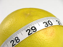 Grapefruit Diet. A measuring tape wrapped around a grapefruit stock photo