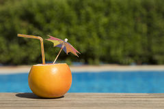 Grapefruit with drinking straw and paper umbrella at the poolside Stock Photo