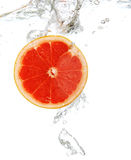Grapefruit dropped into water Royalty Free Stock Photos
