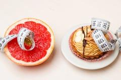 Grapefruit en cake met het meten van band Dieet stock afbeeldingen