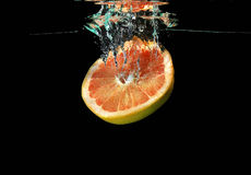 Grapefruit falling into water. Red grapefruit falling into water royalty free stock photos