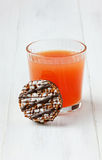 Grapefruit fresh juice with chocolate cookies. On a white wooden surface Royalty Free Stock Photography