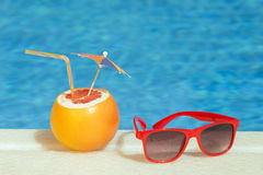 Grapefruit fresh juice drink and sunglasses at the poolside Stock Image