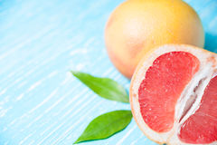 Grapefruit fruits on a blue wooden table. With green leaves, copy space Stock Images