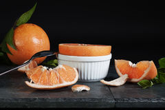 Grapefruit. A halved grapefruit in white bowl with segments, peel pieces, leaves and whole grapefruit in background Stock Photo