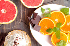 Grapefruit halves and orange slices with mint leaves and chocolate and creamy dessert Stock Photos