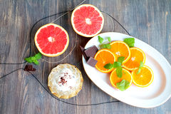 Grapefruit halves and orange slices with mint leaves and chocolate and creamy dessert Royalty Free Stock Photos