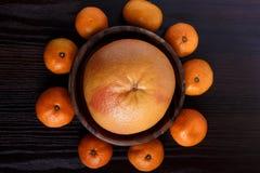 Grapefruit in houten plaat met mandarines op donkere achtergrondclose-upmacro stock foto